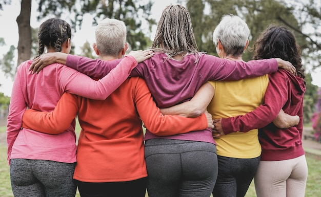 야외에서 서로 껴안고 있는 다세대 여성들의 뒷모습 - 다인종 사람들과 팀워크 개념
