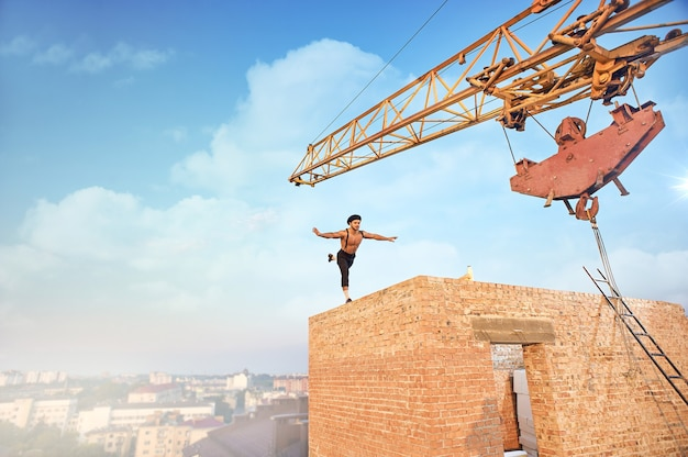 높은 벽돌 벽에서 운동을 하는 근육질의 운동 남자의 뒷모습. 높은 건물을 마무리하지 않습니다. 배경에 큰 철 기중기와 도시 풍경입니다.