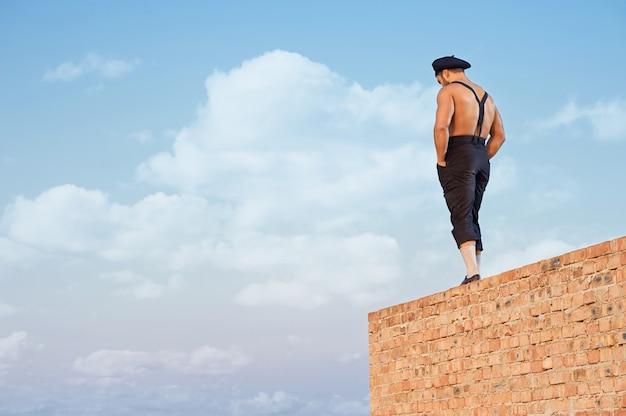 高い上のレンガの壁に立っている作業服の筋肉ビルダーの背面図。ポケットに手をつないで見下ろしている男。暑い夏の日の極端な建物。背景の青い空。