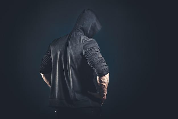 黒の背景の上にスタジオでポーズをとって筋肉の男性ボディービルダーの背面図