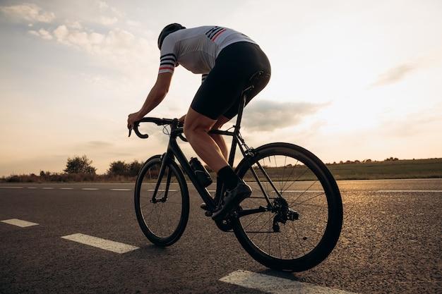 반 구부러진 위치에서 스포츠 의류 및 헬멧 승마 자전거에 근육 질의 남자의 다시보기