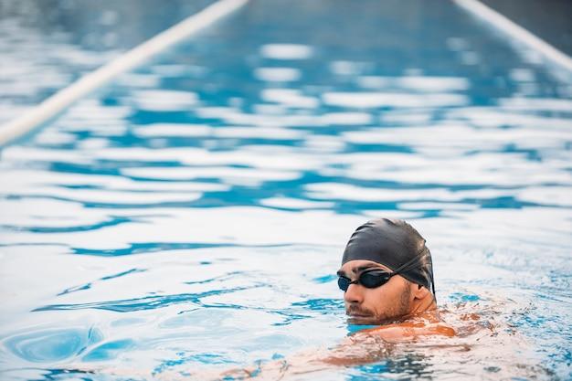 Вид сзади мускулистого пловца в плавательной шапочке и очках, стоящего у бассейна