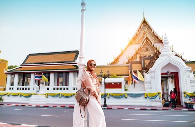 仏教寺院、道路で携帯電話を使用してアジアの女性を歩くイスラム教徒の女性観光客の背面図。旅行のコンセプト。