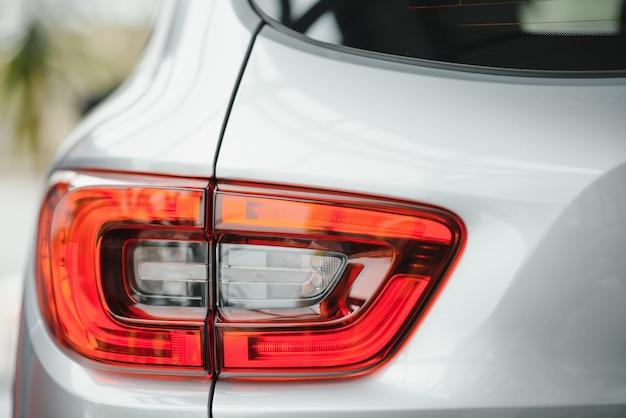 新しい白い車の背面図。車のヘッドライトをクローズアップ。白のプレミアムシティクロスオーバー、高級suvリアライトのクローズアップ。車のランプのクローズアップ。