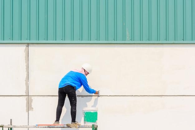 建設現場での塗料のスパチュラ手を使った塗装作業員修理壁の背面図