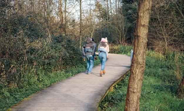 森への木製の小道を走りながら子供たちにおんぶを与える親の背面図