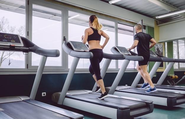 フィットネスセンターでのトレーニングセッションでトレッドミルの上を走っている人々の背面図
