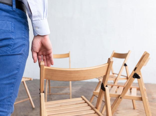 集団療法のために準備された空の椅子を持つ人の背面図