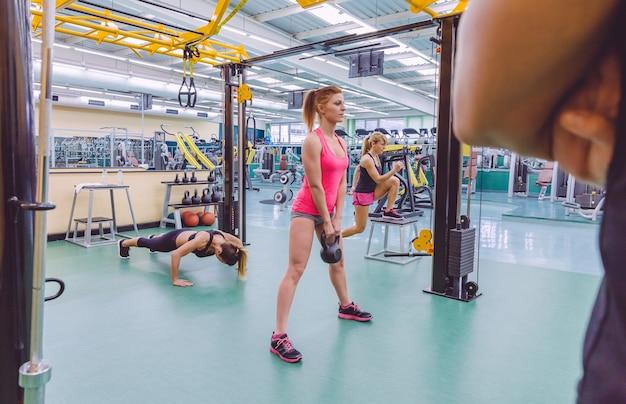 フィットネスセンターのクロスフィットサーキットで一生懸命トレーニングしている美しい女性のグループを見ているパーソナルトレーナーの背面図