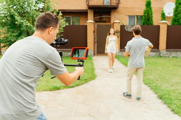 Вид сзади фотографа, делающего фотографию или видео, в то время как доставщик собирается дать коробку доставки женщине, на открытом воздухе, около частного дома.