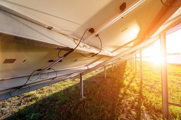 Вид сзади фотоэлектрических солнечных батарей на фоне заката