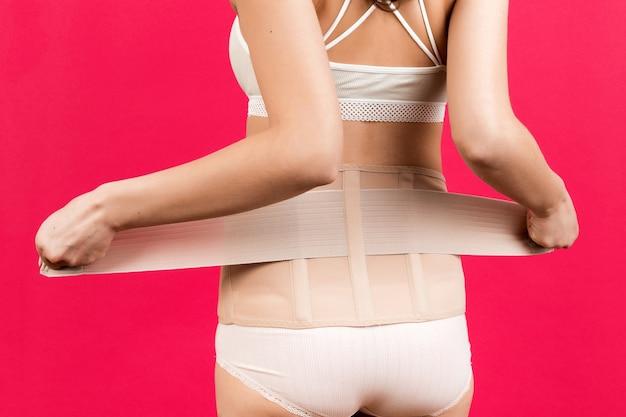 整形外科コルセットをドレッシング妊娠中の女性の背面図