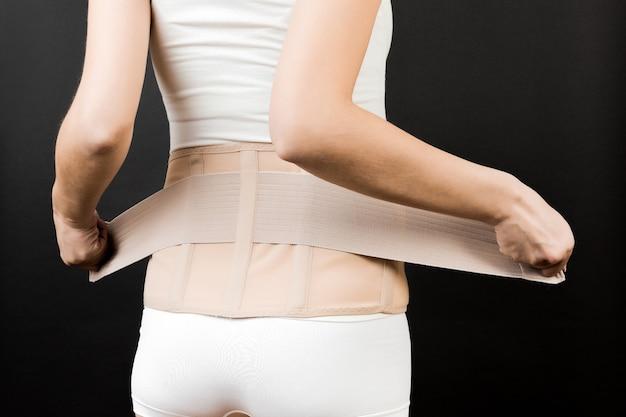 복사 공간이 있는 검은색 배경에서 요통을 줄이기 위해 지지 붕대를 감고 있는 속옷을 입은 임산부의 뒷모습. 정형 복부 지지 벨트 개념의 자른 이미지.