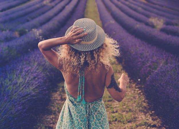 自由奔放に生きるエレガントな青いドレスのかわいいベイビーの背面図旅行スタイルの帽子と金髪の巻き毛の素敵な長い髪を身に着けているラベンダー畑を歩く-アウトドアネイチャーアドベンチャーライフスタイルのコンセプトまたは無料の女性