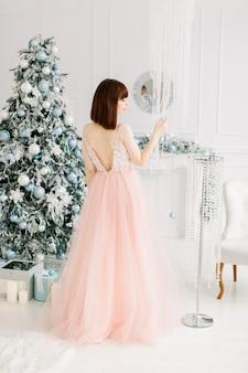 クリスマスツリーの上に立っているイブニングドレスのきれいな女性の背面図