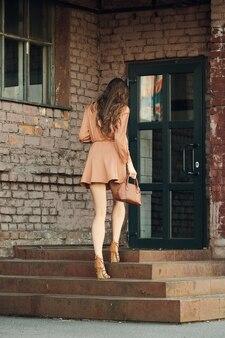 오래 된 건물의 계단을 오르는 예쁜 젊은 여자의 뒷면