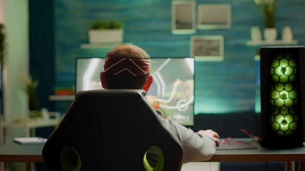 プロゲーマーが自宅からプロの強力なコンピューターでプレイするfpsビデオゲームの新しいグラフィックをテストする背面図。サイバースペースで実行される仮想シューティングゲーム、eスポーツプレーヤーゲームオンライントーナメント