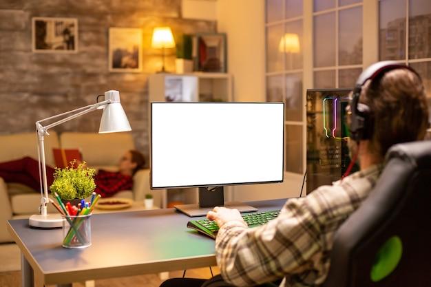 リビングルームで夜遅くに孤立したモックアップ画面でコンピューターを見ているプロのゲーマーの背面図