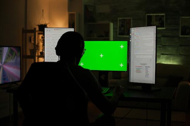 暗い部屋で緑色の画面でコンピューターで遊んでいるプロのゲーマーの背面図。