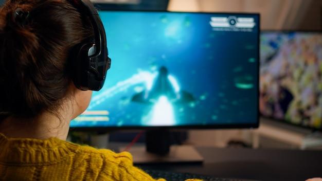 シューティングゲームをプレイしているプロのオンラインゲーマー女性の背面図。最新のストリーミングテクノロジーを使用して、強力なrgbコンピューターでゲームトーナメントをプレイするプロeスポーツチームプレーヤーストリーマー