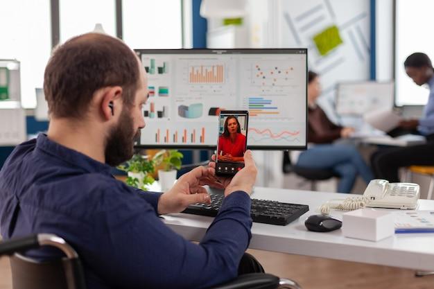 Вид сзади менеджера проекта, держащего смартфон, который слушает удаленную компанию-лидера по видеозвонку, разговаривает онлайн с помощью наушников, обсуждает на виртуальной встрече финансовый проект