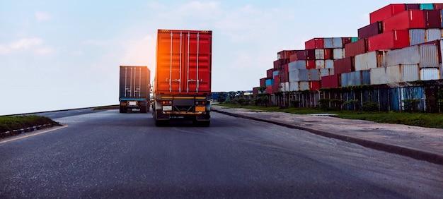 항구 터미널의 선박 항구 물류 운송 산업에서 빨간색 컨테이너 트럭의 후면보기
