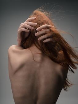 裸の赤毛の女性の背面図