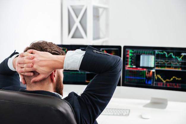 Вид сзади расслабленного бизнесмена, сидящего на рабочем месте с руками за головой