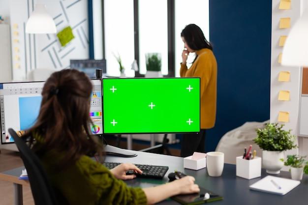 Вид сзади ретушера, работающего над набором фотографий с помощью стилуса в программном обеспечении для редактирования с использованием зеленого экрана, изолированный дисплей компьютера с цветным ключом