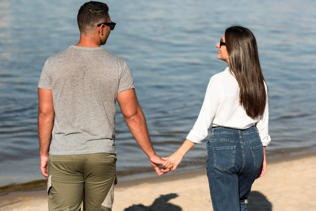 ビーチで手をつないでロマンチックなカップルの背面図
