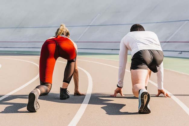 Вид сзади бегунов, занимающих позицию