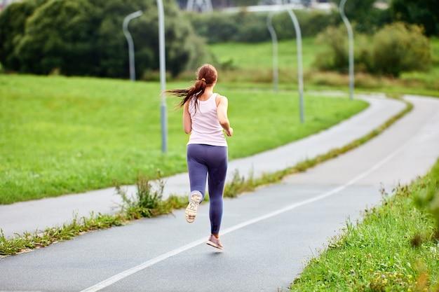 Вид сзади бегущей женщины на дороге летним утром