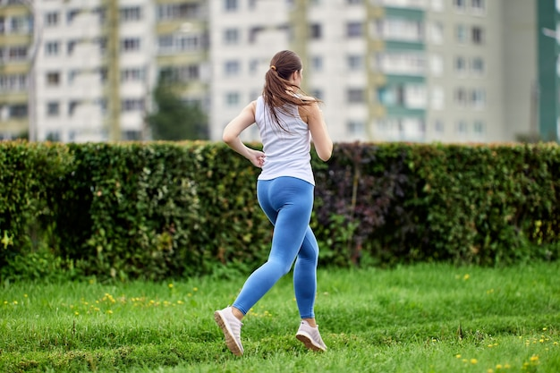Вид сзади бегущей молодой изящной женщины на открытом воздухе