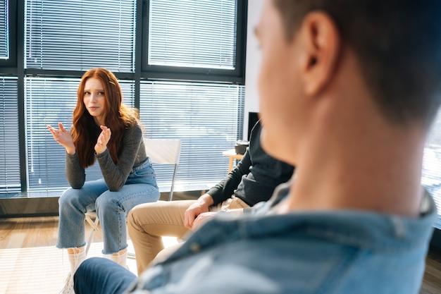 그룹 치료 세션 동안 원에 앉아 있는 다른 환자들과 정신적 문제를 공유하는 슬픈 우는 젊은 여성의 뒷모습. 심리학자와 정신 건강 문제에 대한 그룹 컨설팅의 개념.