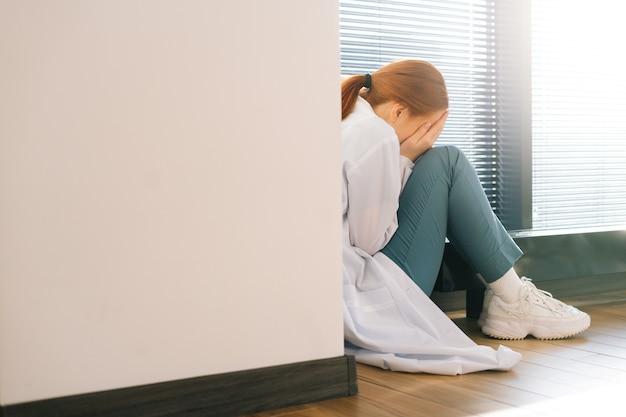 머리와 팔을 무릎에 안고 창가에 앉아 울고 있는 슬픈 우울한 여성 의사의 뒷모습