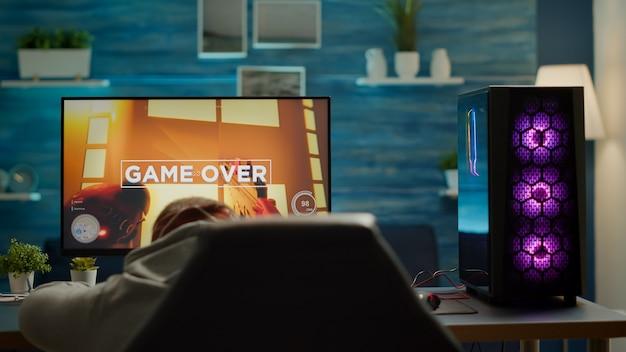 シューターモックアップビデオゲームを失う悲しいプロのeスポーツゲーマーの背面図。強力なパソコンを使用してゲームトーナメント中にオンラインサイバーパフォーマンスをストリーミングするヘッドフォンで敗北した男