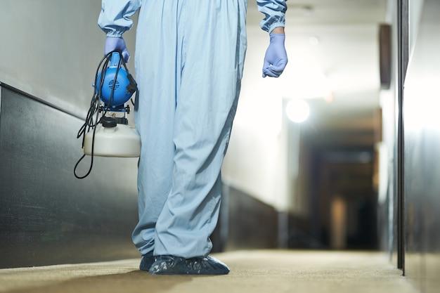 ホテルの表面から細菌を除去するためにスプレーを使用している衛生労働者の背面図。コロナウイルスと検疫の概念