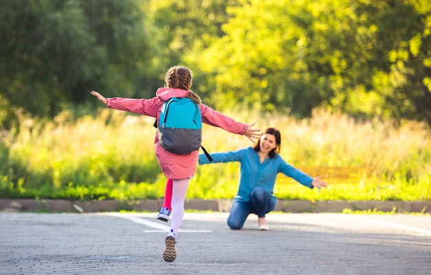 日当たりの良い通りでクラスの後に母親に走っている女子高生の背面図