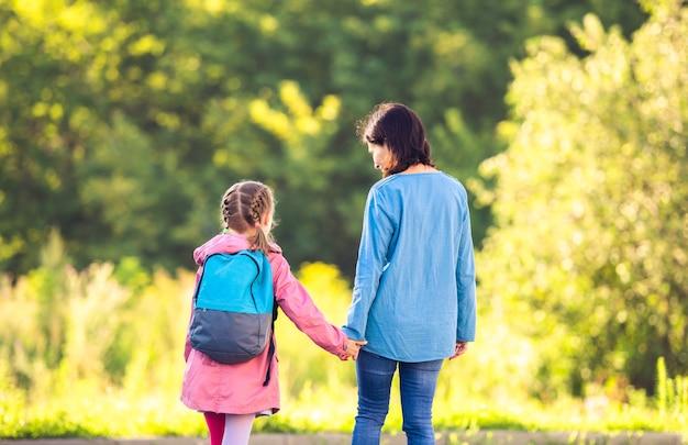 自然に母親の手を保持しているバックパックを持つ女子高生の背面図 Premium写真