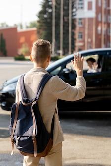 Вид сзади школьника с рюкзаком, машущего рукой его родителю