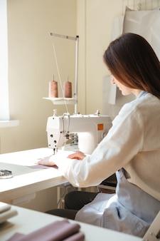 Вид сзади швеи, работающей на швейной машине