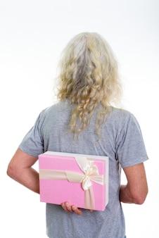 後ろにギフトボックスを隠している先輩のひげを生やした男の背面図