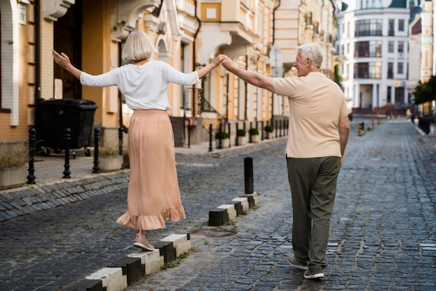 屋外散歩を楽しんでいる年配のカップルの背面図
