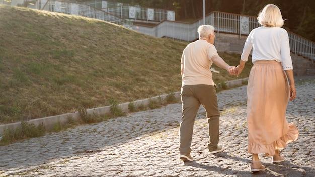 Вид сзади пожилой пары, держась за руки в городе