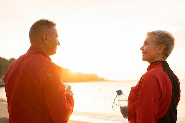ジョギング中にビーチで年配のカップルの背面図