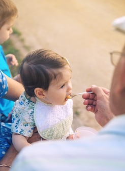 屋外で年配の女性の上に座っている愛らしい女の赤ちゃんにフルーツピューレを食べている年配の男性の背面図。祖父母と孫のライフスタイルの概念。