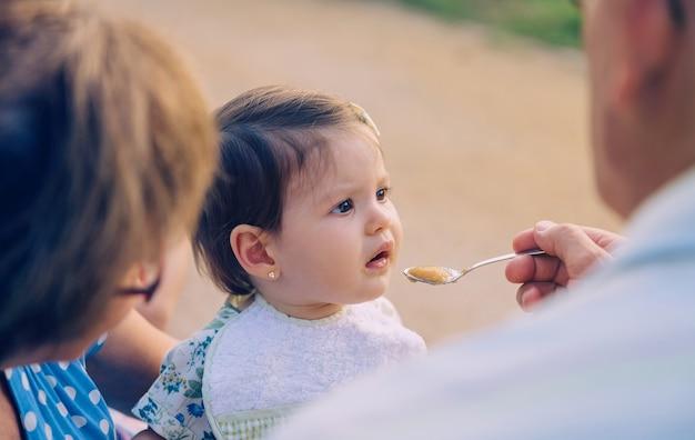 Вид сзади старшего человека, кормящего фруктовым пюре очаровательной девочкой, сидящей над пожилой женщиной на открытом воздухе. концепция образа жизни бабушек и дедушек и внуков.