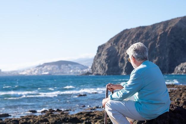 体の痛みのために杖を持ってビーチに夕日の光に座って、水の上の地平線を見ている年配の男性の背面図