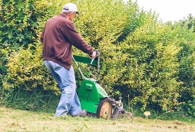 フィールドで芝刈り機で芝生を刈るキャップを持つ年配の男性の背面図