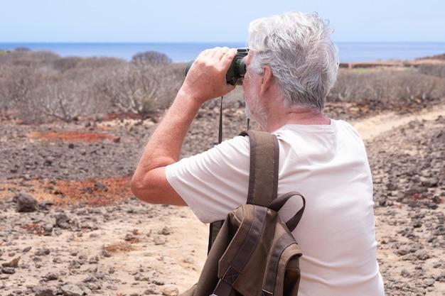 야외 트레킹에서 배낭을 메고 쌍안경을 들고 멀리 바라보는 백발 노인의 뒷모습